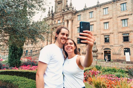 A young couple taking a fancy selfie in a garden in front of an old building