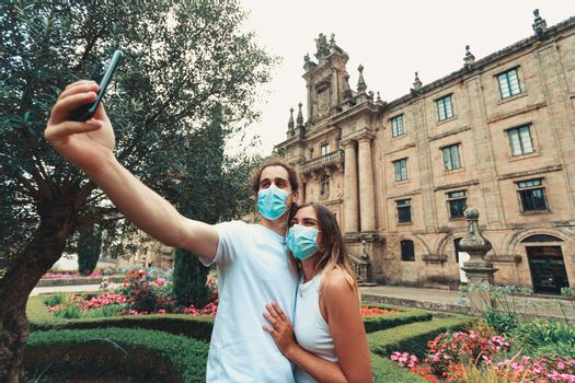 A young couple taking a fancy selfie with the masks on in a garden in front of an old building