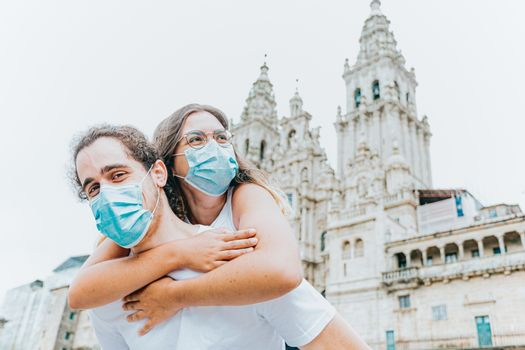 A young and happy couple with the masks put on in front of an ancient cathedral while traveling
