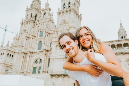 A young couple smiling to camera with the woman over the man in front of a touristic place
