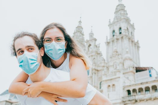 A young couple smiling with the masks on while visiting and old part of the city