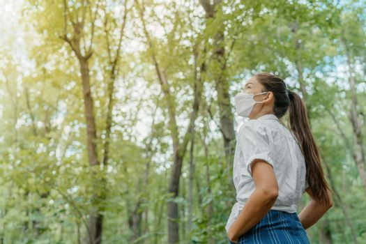 Eco-friendly sustainable face mask. Woman wearing kn95 korean masks walking in outdoor forest lookin up at sunlight. Hope concept for environment. Coronavirus covering.