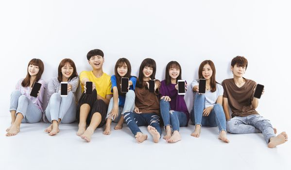 young group showing the smartphones screen and  sitting on the floor