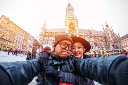 Young Couple Tourists selfie with mobile phone near the  Marienplatz town hall and Frauenkirche in Munich, Germany