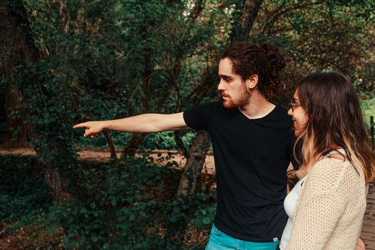 A young man points out something in the forest to his partner