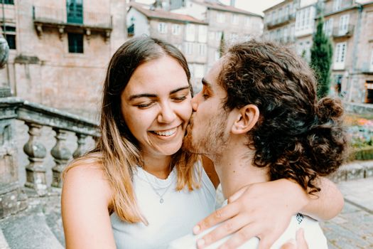 Young man kissing his girlfriends while she smiles