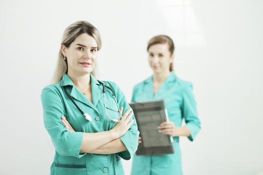 Two female doctors or nurses looking at the camera. Stethoscope phonendoscope on the neck. Holds a folder in his hands