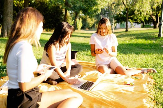 Three beautiful young female caucasian friends sitting on the grass at the park in the morning using smartphone - New technology habits of people - Using internet outdoor to smart working