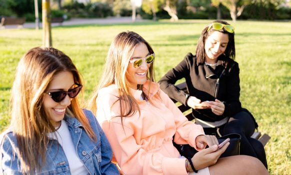 Modern young women sitting on a bench in a green parque using smartphone to stay connected with social network - Female friends are shopping online surrounded by nature in contrast with technology
