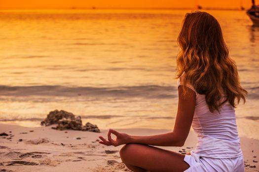 Yoga woman in lotus pose on sea coast at sunset