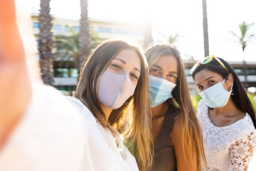 Cute blonde young woman take a selfie with her two female friends wearing the Coronavirus protection mask - New normal life with Covid-19 pandemic using social network connections