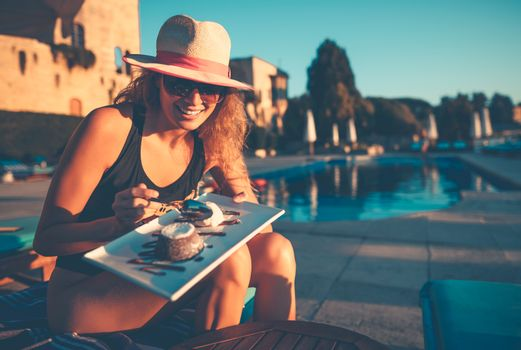 Pretty Woman With Pleasure Eating Tasty Sweet Dessert near the Pool on the Beach Resort. Enjoying Happy Active Summer Vacation.