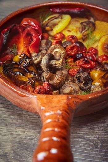 Frying Pan on the Wooden Table with Delicious Grilled Vegetables. Delicious Dish Baked in the Oven. Healthy Organic Vegetarian Food.