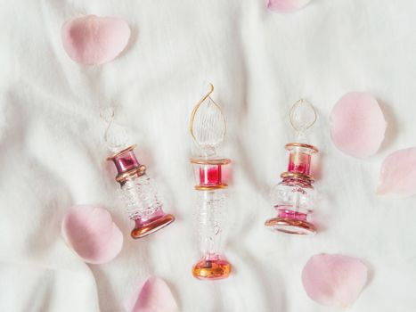 Three graceful bottles for perfume on white crumpled fabric. Top