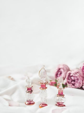 Three graceful bottles for perfume or essential oil on white cru