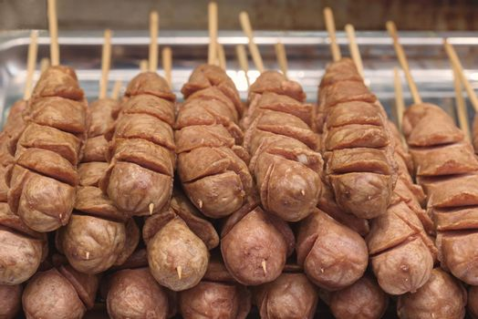 Street food asia. Sausages on a stick.