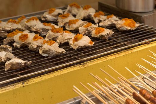Street food asia. Grilled seafood. Oysters on the grill. Chinese street food