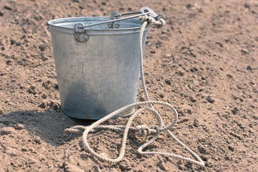 Bucket on the ground. Empty metal bucket