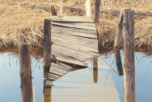 Broken wooden bridge. Water overflow on a broken wooden bridge