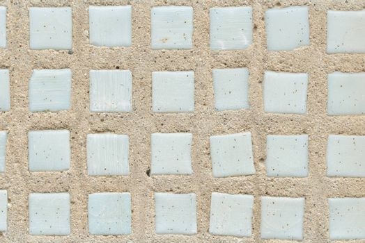 Concrete wall with mosaic. Old white mosaic tiles
