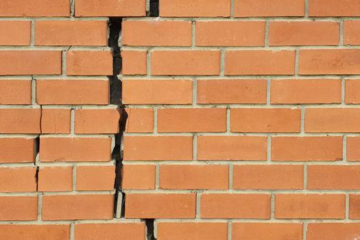 Cracked brick wall. Broken brick wall background
