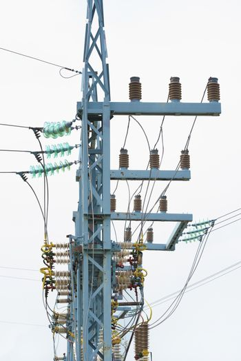 Electric pole on a white background. Garland of insulators on electric wires of high-voltage support