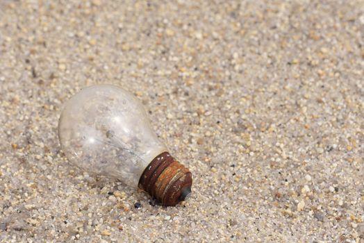 Electric light bulb on sand. Old light bulb on the floor