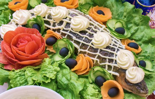 Baked fish decorated with vegetables. Fish and vegetables on the table.