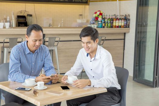 Two Asian businessmen discussing while having coffee together