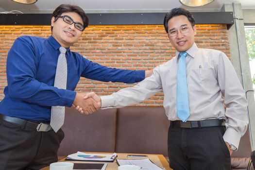 Two Asian businessmen handshake and congratulate during discussion outside office