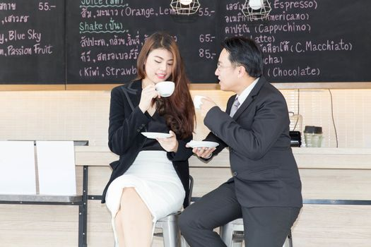 Two Asian businessmen and businesswoman discussing while having coffee together