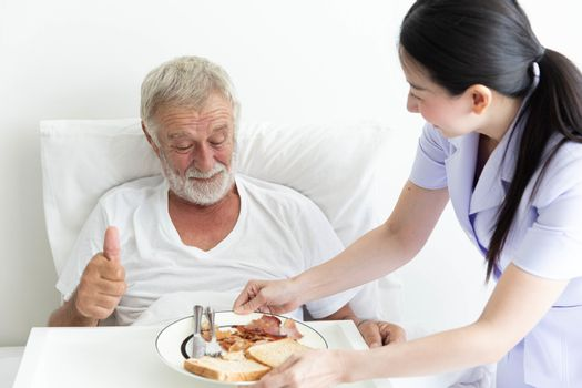 Young female nurse take care a senior retirement male serving breakfast on bed and old man love it