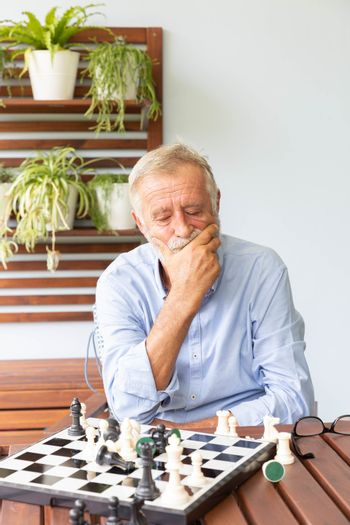 Senior retirement man playing chess with himself at home