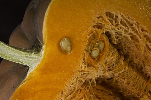 Cut ripe orange pumpkin close up on black background