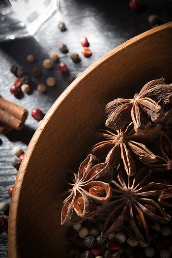 Anise stars and peppercorns in a wooden dish