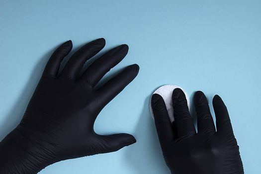 Hands in black nitrile gloves with a cotton sponge on a blue background