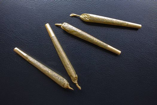 Cannabis Pre-Roll Joints Cigarettes on a leather black texture.