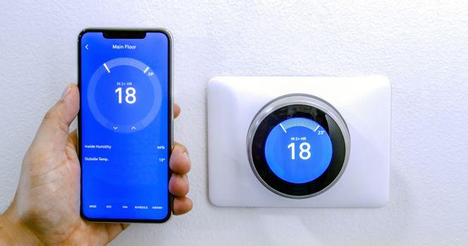 Calgary, Alberta, Canada. Aug. 29, 2020. A person cooling down with air conditioner with a iPhone 11 Pro Max using the nest app on celsius metrics using a wireless Nest Learning Thermostat on a white wall.