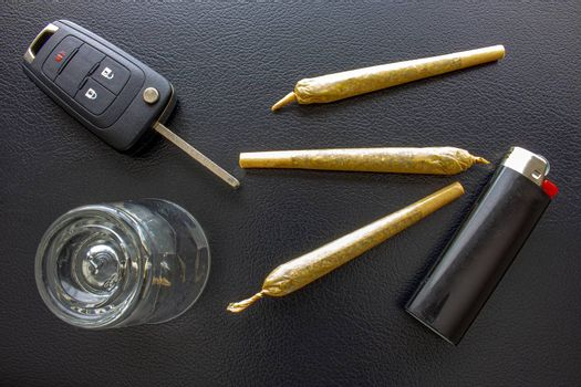 Cannabis Joints Cigarettes with car key, a shoot glass and a lighter on a leather black texture. Concept driving high. Drug-impaired driving is dangerous and against the law