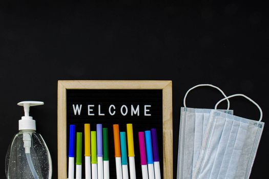 A black board with the text Welcome and markets colors with a hand sanitizer and face masks on a black background