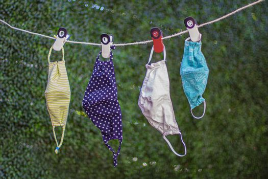Drying outside reusable family face masks, hang on a clothesline nylon rope with clothespins.