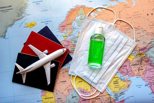 Passports with a plane and face mask and hand sanitizer on a world map. Concept traveling on a place during a global pandemic. Trave durin covid 19.l