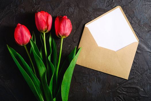 Red bunch of tulip flowers with envelope card on textured black background, top view copy space