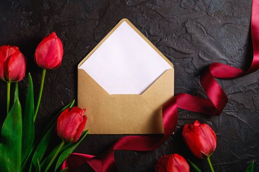 Red bunch of tulip flowers with envelope card and ribbon on textured black background, top view copy space