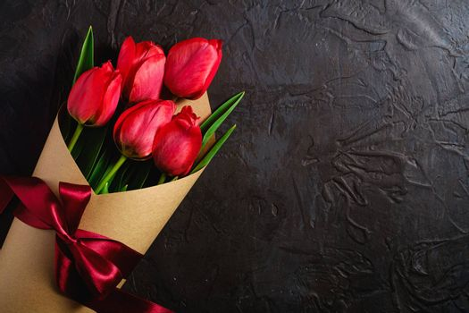 Bouquet with bow-knot ribbon of red tulip flowers on textured black background, top view copy space