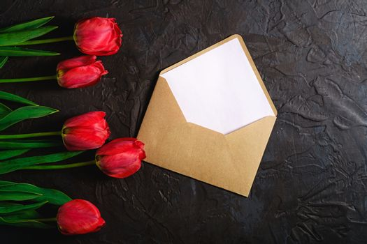 Row of tulip flowers with envelope on textured black background, top view copy space