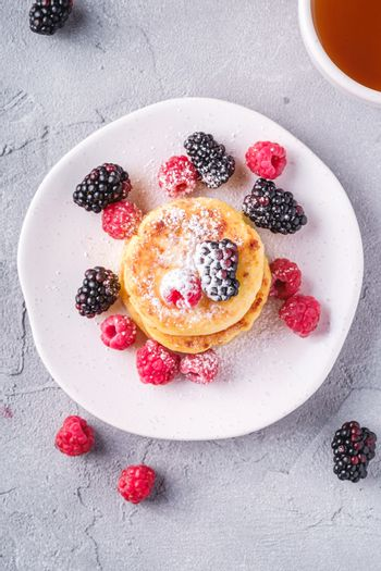 Cottage cheese pancakes and powdered sugar, curd fritters dessert with raspberry and blackberry berries in plate near to hot tea cup with lemon slice on stone concrete background, top view
