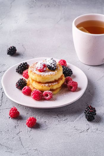 Cottage cheese pancakes and powdered sugar, curd fritters dessert with raspberry and blackberry berries in plate near to hot tea cup with lemon slice on stone concrete background, angle view