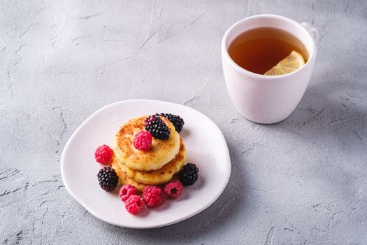 Cottage cheese pancakes, curd fritters dessert with raspberry and blackberry berries in plate near to hot tea cup with lemon slice on stone concrete background, angle view