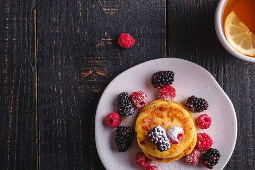 Cottage cheese pancakes, curd fritters dessert with raspberry and blackberry berries in plate near to hot tea cup with lemon slice on dark black wooden background, top view copy space